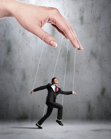tiedup: Businessman marionette on ropes controlled by puppeteer
