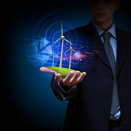 Business man and a windmills as a symbol of green energy Stock Photo