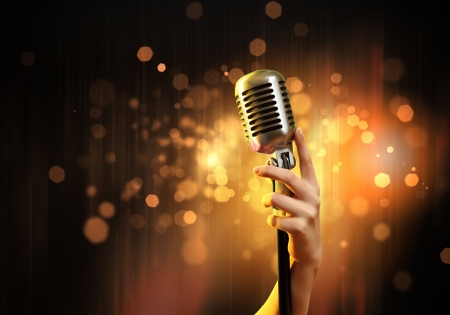 microfono antiguo: Mano femenina que sostiene un micrófono retro solo contra el fondo colorido Foto de archivo