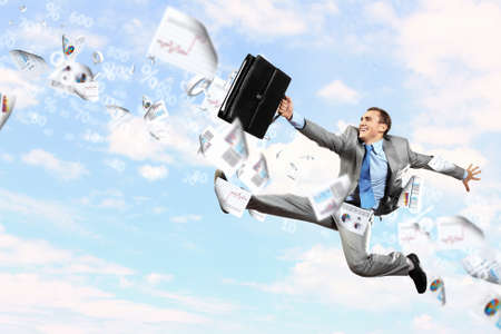 Image of a businessman jumping high against blue sky background photo