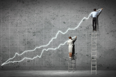 businesspeople standing on ladder drawing diagrams and graphs on wall Stock Photo - 18241869