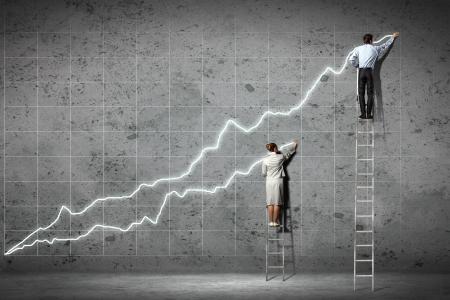 escaleras: hombres de negocios de pie en los diagramas de escalera de dibujo y gr�ficos en la pared