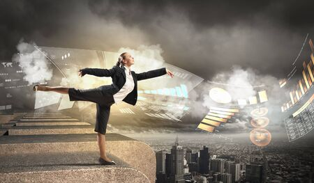 Image of pretty businesswoman balancing on the roof above cityscape Stock Photo - 18241798