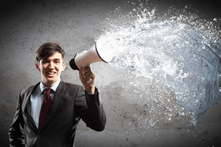 young businessman smiling in black suit holding megaphone photo