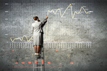 businesswoman standing on ladder drawing diagrams and graphs on wall Stock Photo - 18241880
