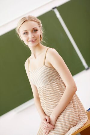 Young female teacher standing near blackboard at school Stock Photo - 18241775