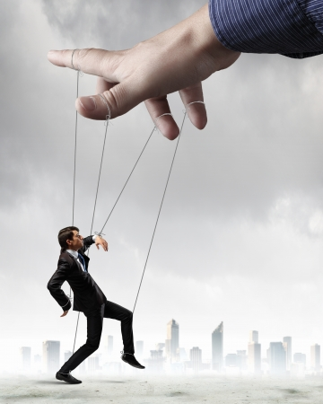 manipulation: Businessman marionette on ropes controlled by puppeteer against city background