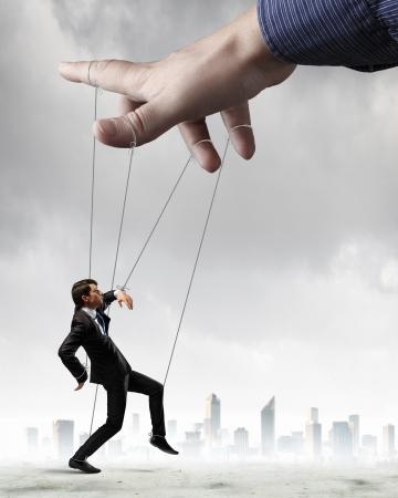 marionetta: Imprenditore marionetta su corde controllata dal burattinaio su sfondo citt?