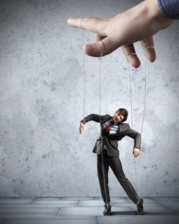 controlled: Businessman marionette on ropes controlled by puppeteer