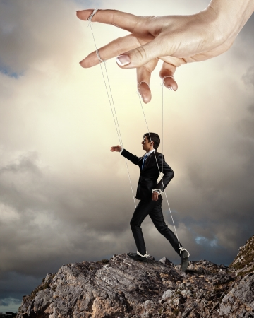 tiedup: Businessman marionette on ropes controlled by puppeteer standing atop of mountain