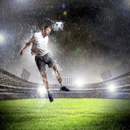 football player in white shirt striking the ball with head at the stadium under the rain Imagens