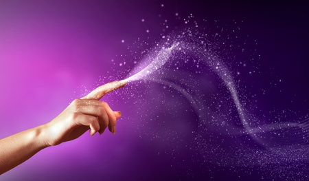 finger nails: magical hand conceptual image with sparkles on colour background