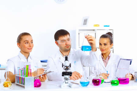 Team of scientists working with liquids in laboratory photo