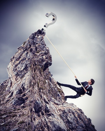 businessman climbing mountain with question sigh on top