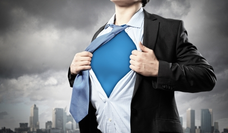heroism: Image of young businessman showing superhero suit underneath his shirt standing against city background Stock Photo