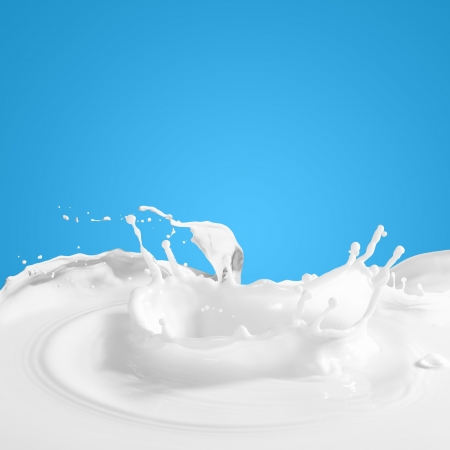 tomando leche: Verter la leche splash blanco sobre fondo de color Foto de archivo