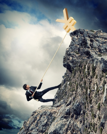 businessman climbing mountain with yen on top photo