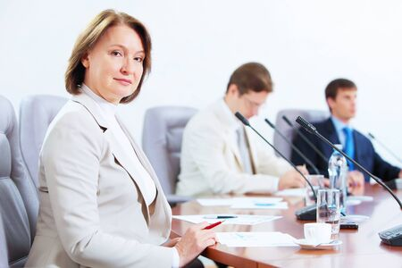 Image of three businesspeople sitting at table at conference Stock Photo