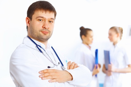 Young male doctor in white uniform with collegues on the background Stock Photo - 18394114