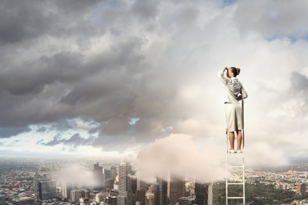 reaching hands: Businesswoman standing on ladder looking into distance against city background