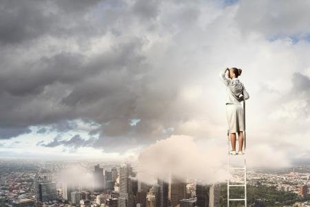 reaching hands: Zakenvrouw staande op de ladder op zoek naar afstand tegen stad achtergrond
