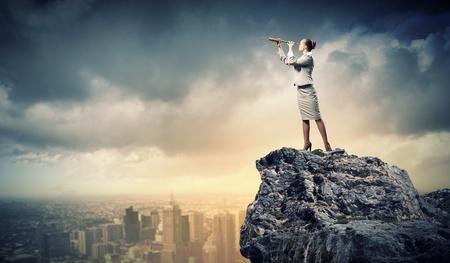 marketanalyze: Image of businesswoman looking in telescope standing a top of rock