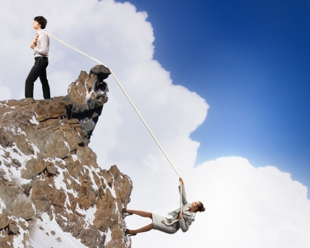 pulling rope: Image of busionessman and businesswoman pulling rope atop of mountain Stock Photo