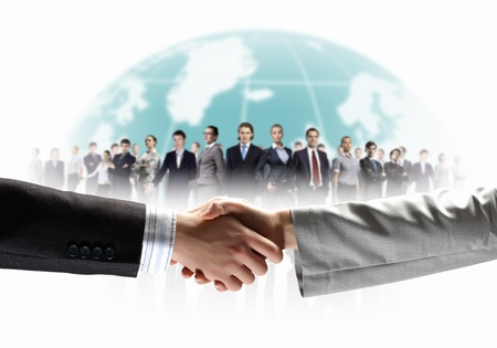 teamwork together: business handshake against white background and standing businesspeople Stock Photo