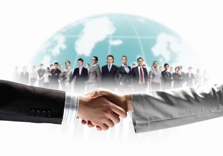 zusammenarbeit: Business-Handshake vor wei�em Hintergrund und Stehen Gesch�ftsleute