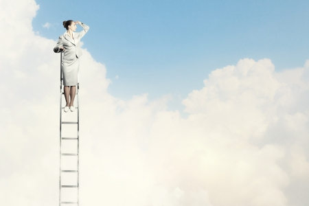 ambitions: Businesswoman standing on ladder looking into distance against cloudy background