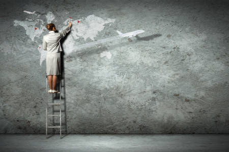 Businesswoman standing on ladder and pointing on map picture on wall Stock Photo - 18472193