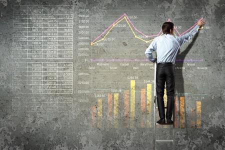 estadisticas: hombre de negocios de pie en los diagramas de escalera de dibujo y gr�ficos