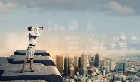 marketanalyze: Image of businesswoman looking in telescope standing a top of building