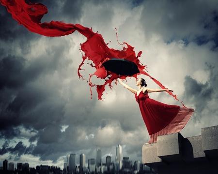 balletdanser in vliegende satijnen jurk met paraplu onder de verf