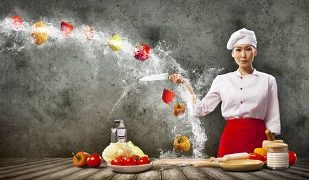 Asian female cook with knife cutting fruits and vegetables in air photo