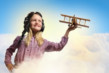 inair: Image of little girl in pilots helmet playing with toy airplane against clouds background Stock Photo