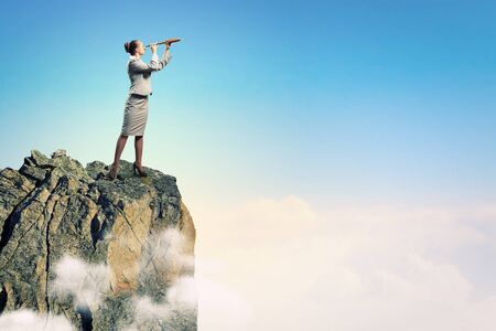 future success: Image of businesswoman looking in telescope standing atop of rock Stock Photo