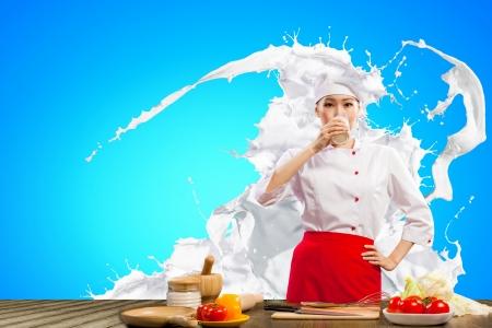 Asian Köchin gegen Milch spritzt in roter Schürze gegen farbigen Hintergrund Trinkmilch Standard-Bild