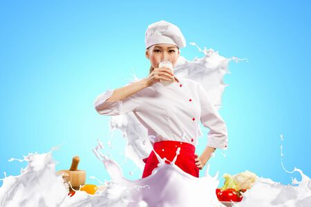 Asian female cook against milk splashes in red apron against color background drinking milk photo