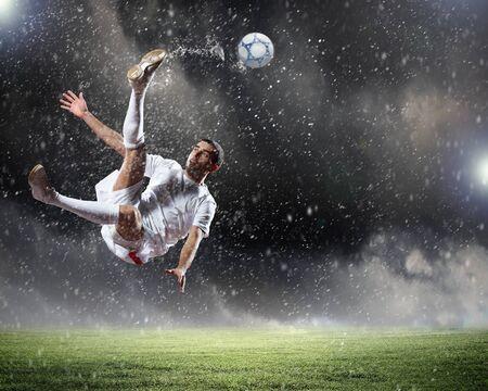 football player in white shirt striking the ball at the stadium under rain photo