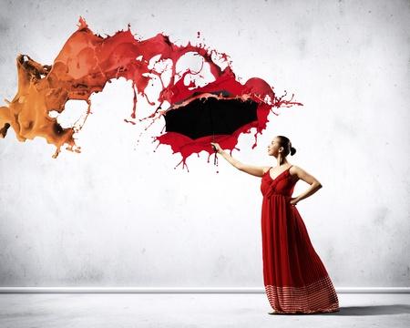danza moderna: bailarín de ballet en vuelo raso vestido con paraguas debajo de la pintura