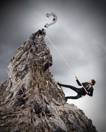 careerist: businessman climbing mountain with question sigh on top