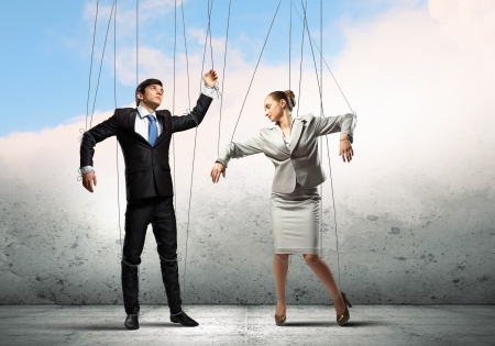 marionette: Image of businesspeople hanging on strings like marionettes  Conceptual photography Stock Photo