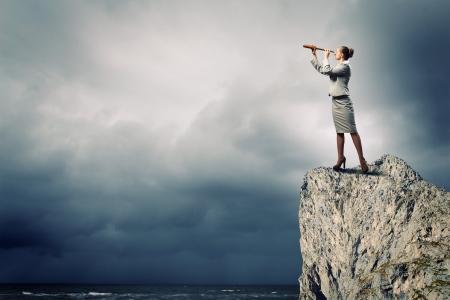Imagen de la empresaria que mira en telescopio de pie encima de la roca Foto de archivo