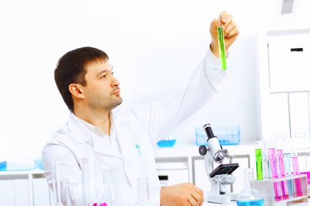 Young male scientist working with liquids in laboratory photo