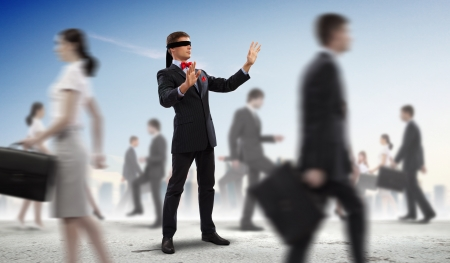 Image of businessman in blindfold walking among group of people photo
