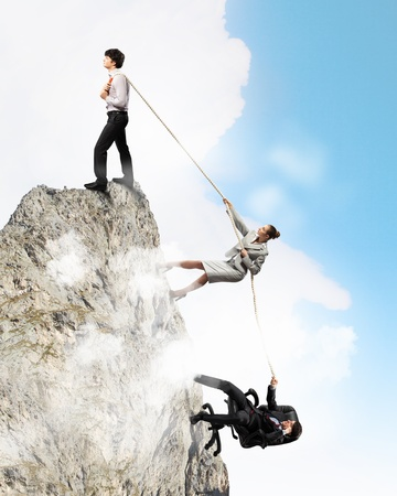 atop: Image of three businesspeople pulling rope atop of mountain Stock Photo