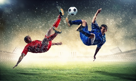 football grass: two football players in jump to strike the ball at the stadium