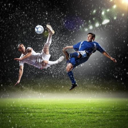 two football players in jump to strike the ball at the stadium under rain photo