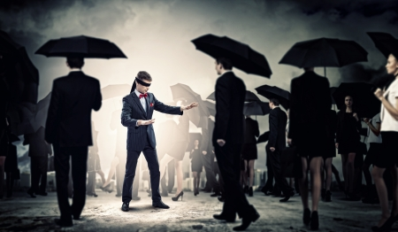 unsure: Image of businessman in blindfold walking among group of people Stock Photo